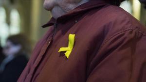 Una mujer, con un lazo amarillo en la solapa.