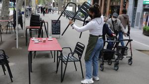 Una mujer organiza la terraza del bar en el que trabaja, en la rambla del Poblenou.