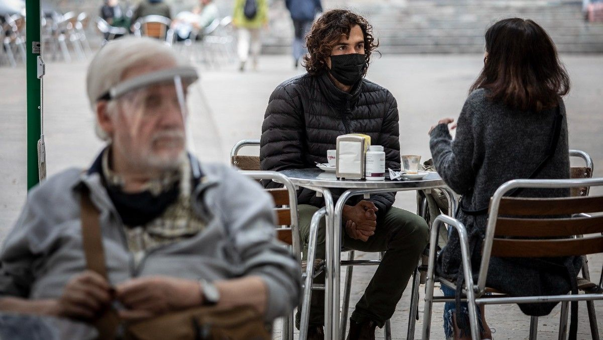 Un hombre lleva mascarilla en la terraza de un bar, en Barcelona.