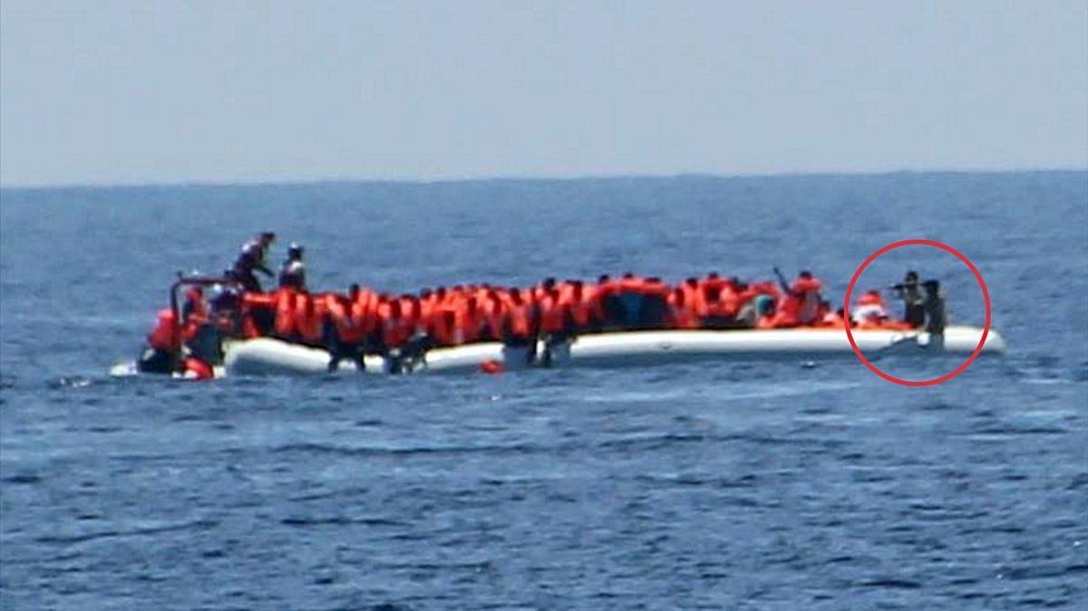 Unos guardacostas libios apuntan con sus armas a un grupo de inmigrantes y refugiados que navegan en una barca por el Mediterráneo, el 24 de mayo.