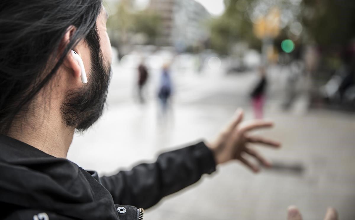Un hombre con auriculares en las orejas, por las calles de Barcelona.