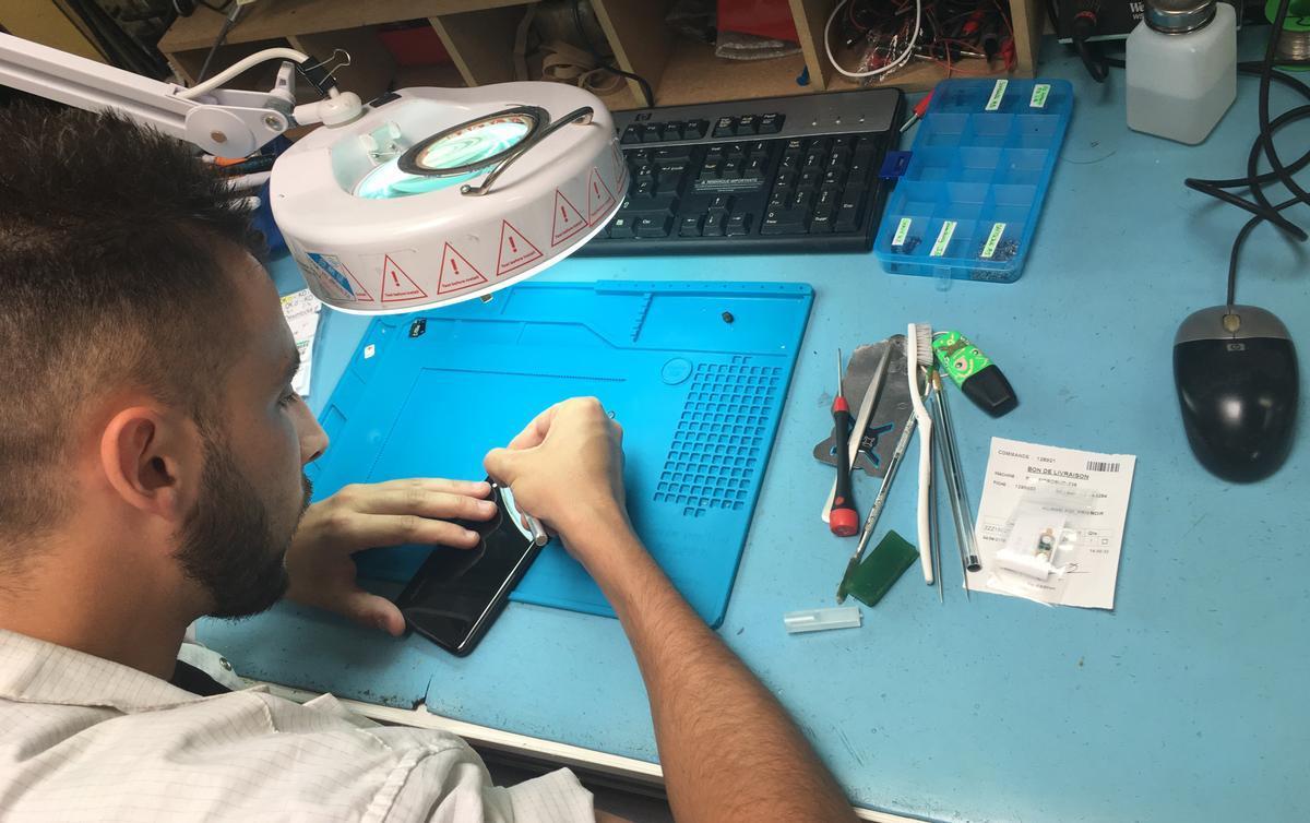 Operario de Smaaart repara teléfono móvil.