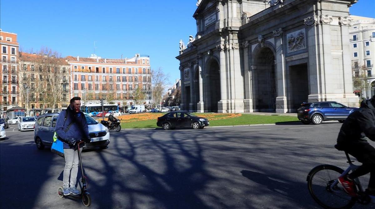 Los patinetes, fuera de las aceras por ley. En la foto, un hombre va en patinete eléctrico por la calzada de la rotonda de la Puerta de Alcalá, en Madrid.