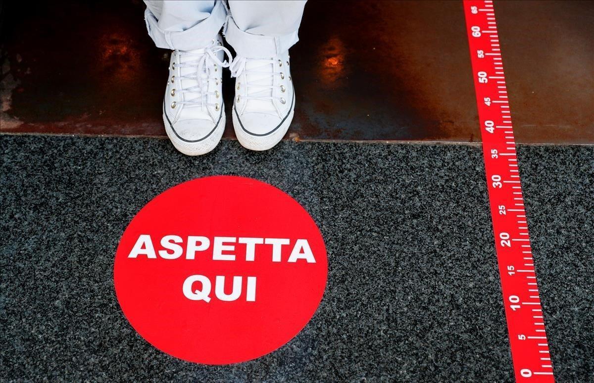 Marcadores de distanciamiento social en la entrada de un café cerca del Coliseo.