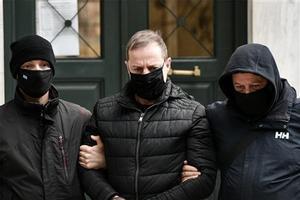 Policías de paisano escoltan al actor y director Dimitris Lignadis, esposado, al despacho de un magistrado en Atenas.