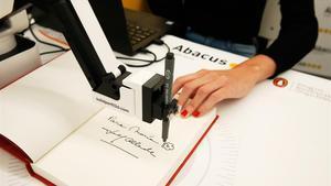Isabel Allende firma libros en la librería Abacus de Enric Granados vía internet y brazo robotizado.