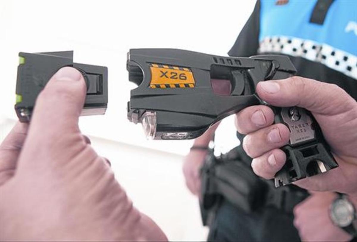 Un policía local de Sant Andreu de Llavaneres muestra una pistola eléctrica.