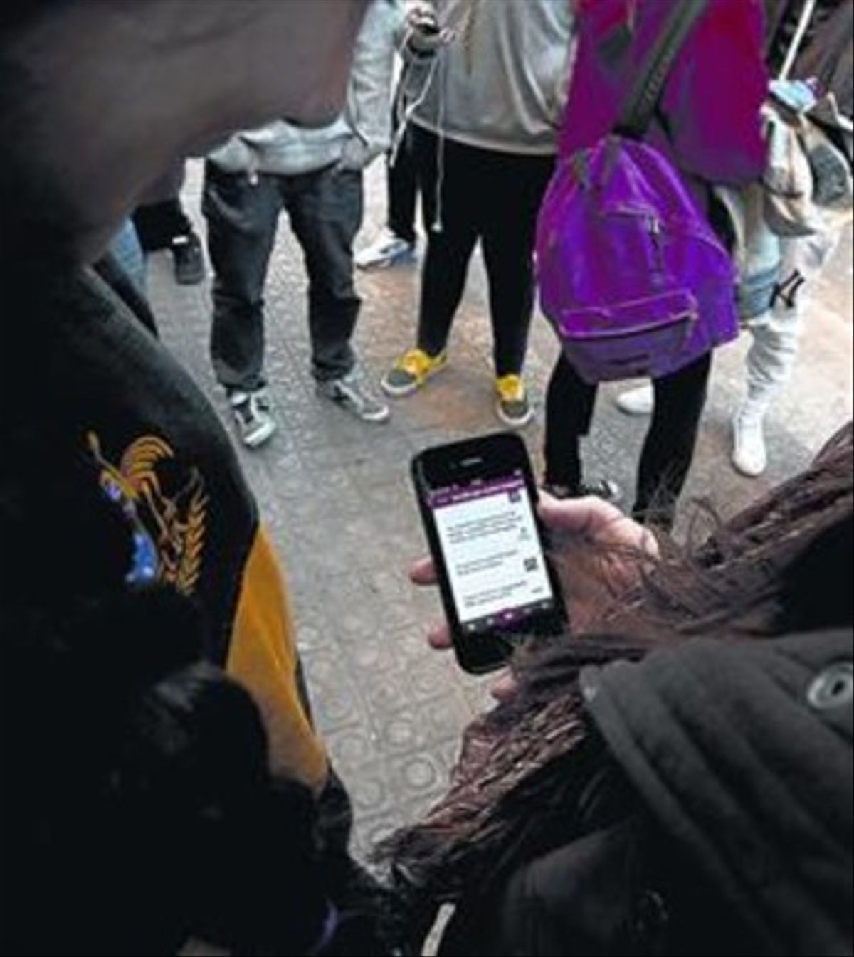 Unos usuarios consultan una aplicación en un teléfono móvil.