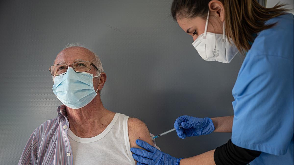 Una sanitaria vacuna a un paciente contra el covid-19, en Barcelona.