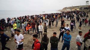 Cientos de personas esperan en la playa de la localidad de Fnideq (Castillejos) para cruzar los espigones deCeutaeste martes.