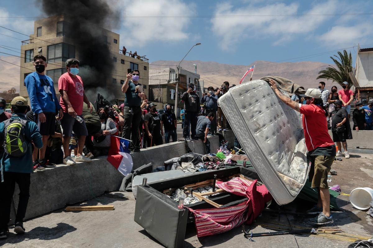 Un grupo de personas quema carpas utilizadas por extranjeros para pernoctar en plazas y playas, durante una marcha contra la migración irregular en Iquique.