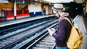 Joven utilizando susmartphone esperando el tren