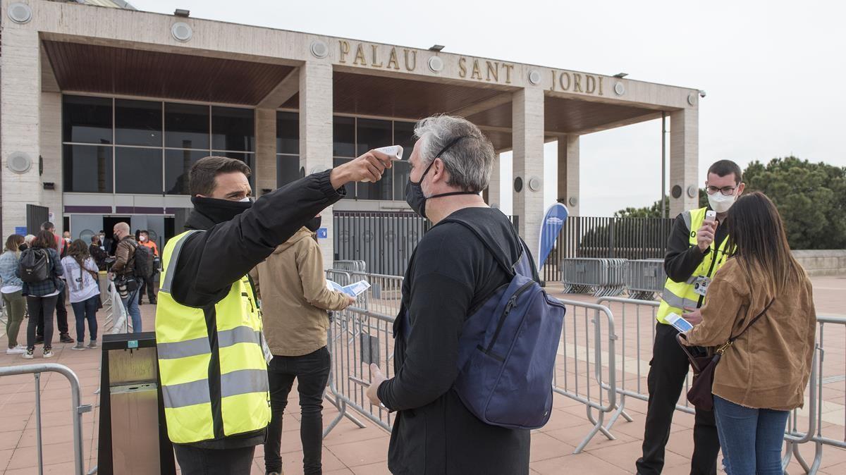 Personal del Sant Jordi mide la temperatura de los asistentes al concierto multitudinario de Love of Lesbian en la entrada del recinto, el pasado 27 de marzo.