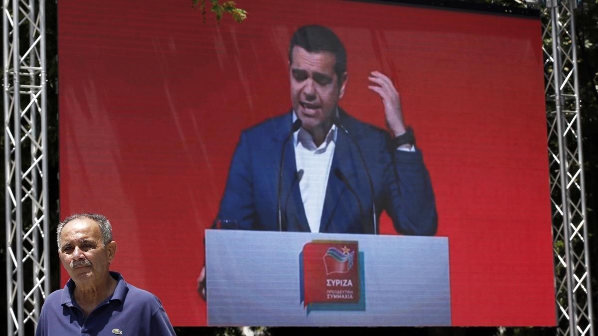 Un hombre pasa frente a una pantalla en la que se proyecta un mitin de Tsipras en Atenas, el pasado 18 de mayo.