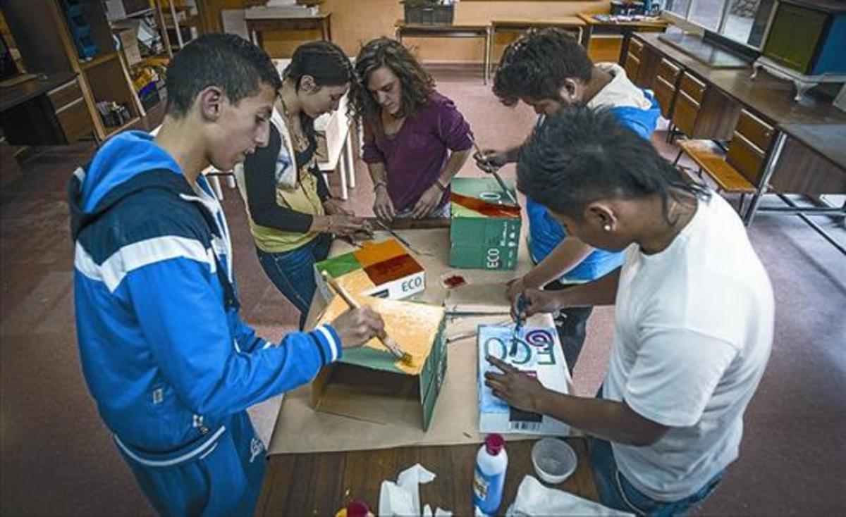Salida 8 La voluntaria Meri (de granate) prepara material para las colonias con unos chicos en El Submarí.
