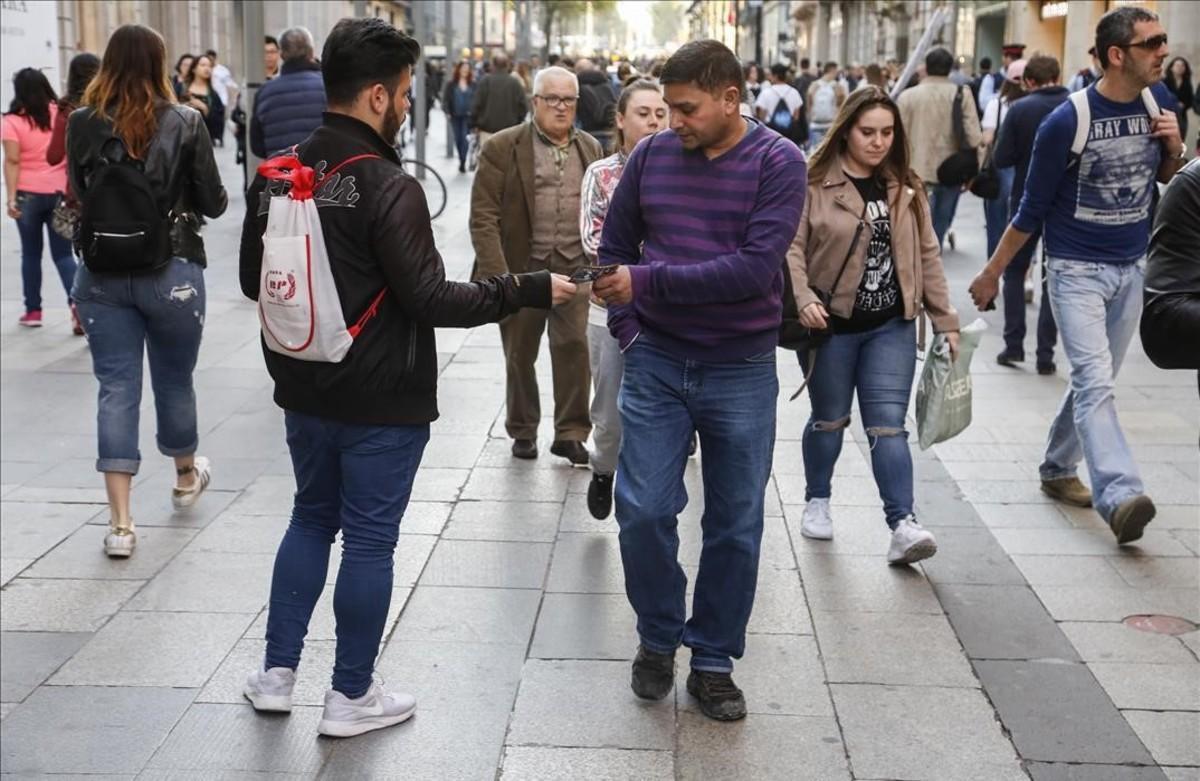 Reparto de folletos en el centro de Barcelona.
