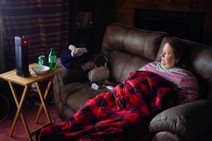 Una mujer se protege del frío con una manta y una pequeña estufa en su casa de Fort Worth.