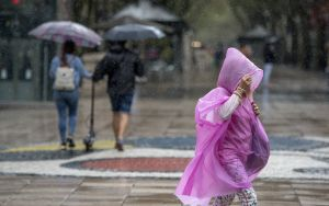Varias personas se protegen de la lluvia, en las Ramblas de Barcelona.