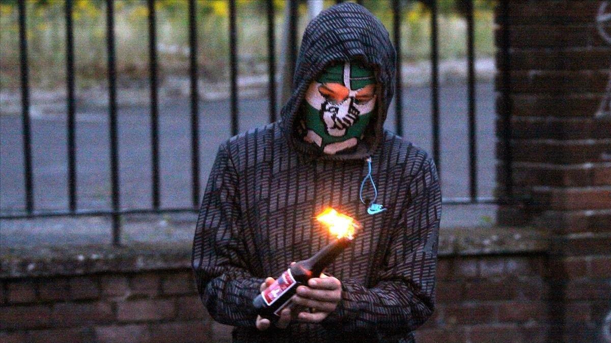 Imagen del 2010 de un joven que prepara un coctel molotov en el barrio deArdoyne, en el norte de Belfats.