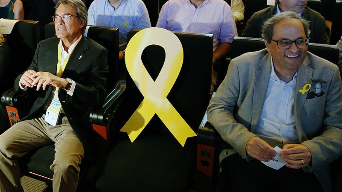 Artur Mas y Quim Torra flanquean un lazo amarillo en representación de Carles Puigdemont en un acto del PDECat.