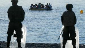 Legionarios españoles frente a ciudadanos marroquís en un bote, en la playa de El Tarajal, cerca de la la valla que separa España de Marruecos.