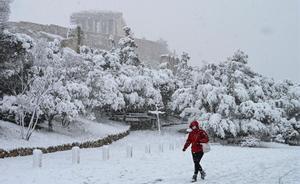 El temporal Medea cubre Atenas de nieve. En la foto, una mujer camina cerca del Partenón.