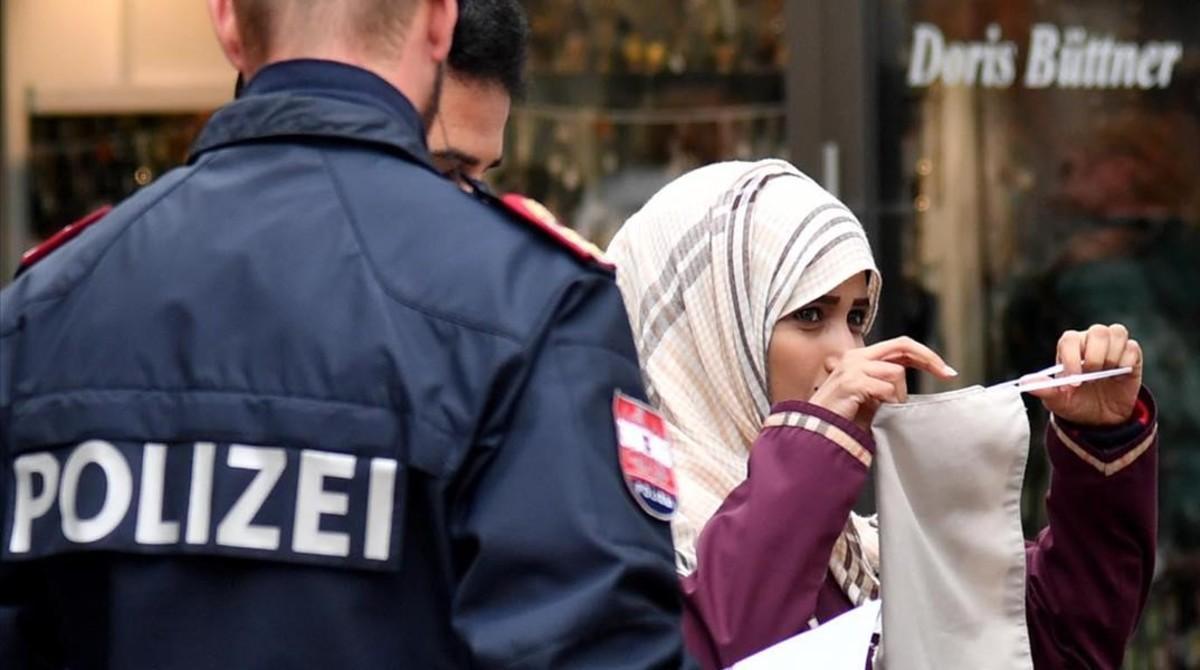 Un policía ordena a una mujer musulmana que se retire el velo en Austria, en octubre del 2017.