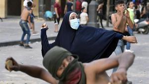 Unos jóvenes lanzan piedras a la policía en una de las protestas de esta semana en Beirut.