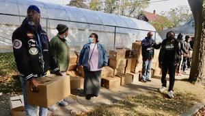 Un grupo de voluntarios reparten cajas de comida en el barrio que mas hombres negros encarcela de EEUU.