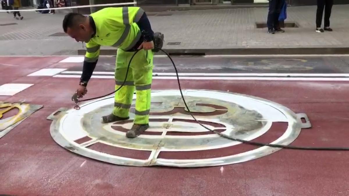 Operarios pintan señales de limitación de velocidad en el asfalto en la calle Borrell con Provença.