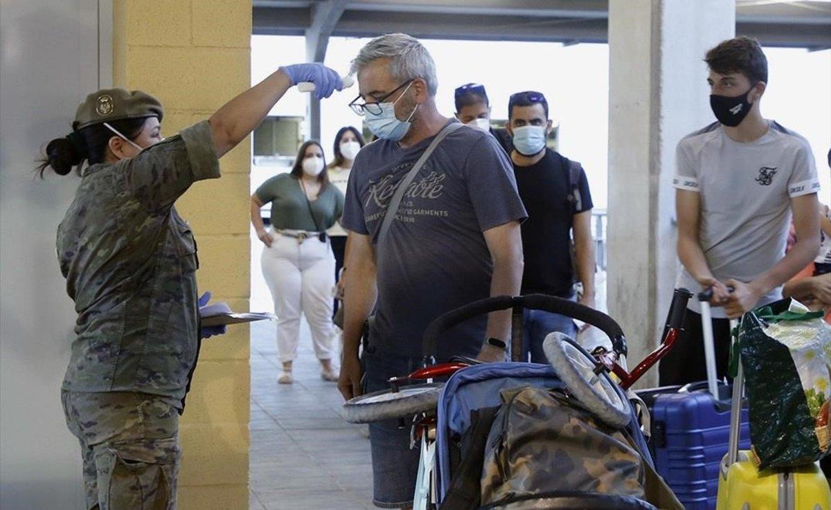 Una enfermera del Ejército toma la temperatura a los pasajeros del barco procedente de Málaga durante un control sanitario a su llegada a Melilla, el 19 de junio.