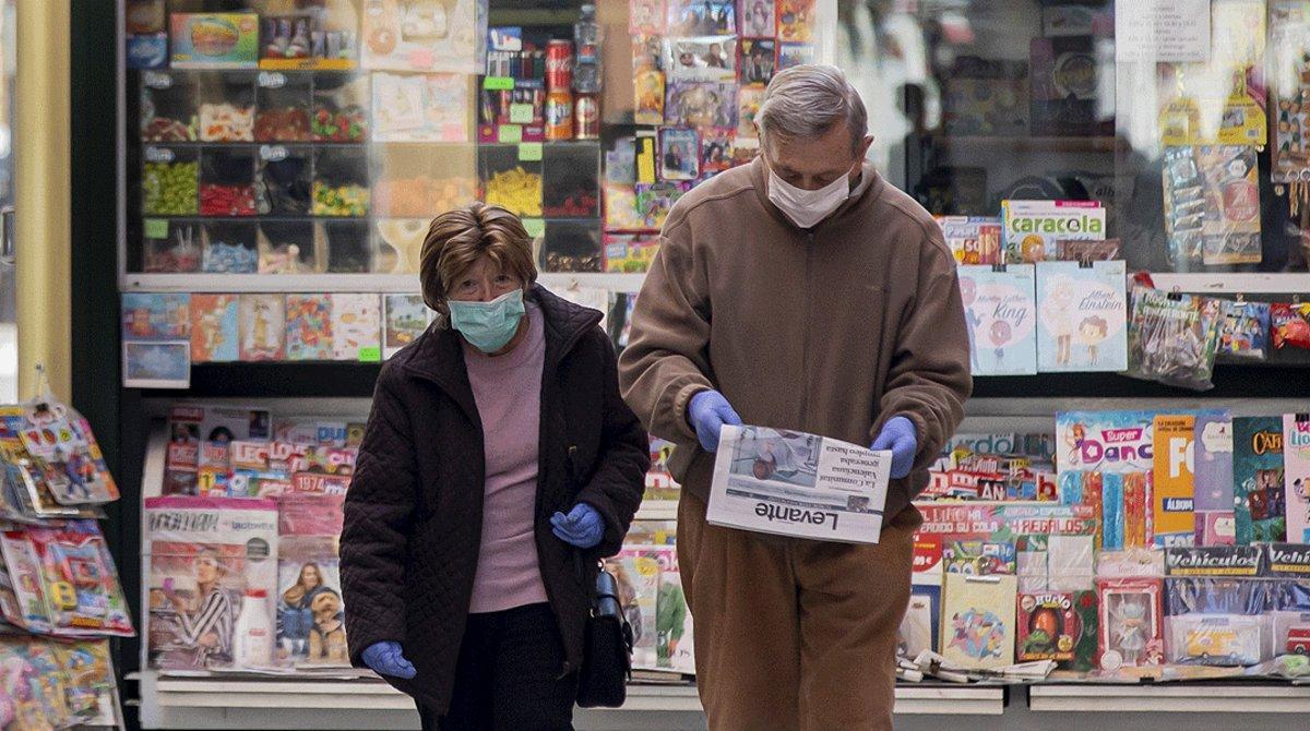 Una pareja pasea tras comprar un diario en un quiosco, el pasado abril, en pleno confinamiento, en València.