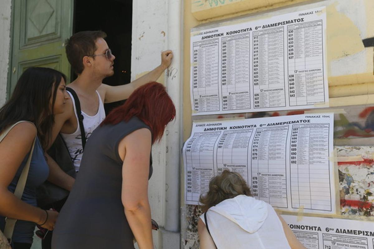 Varios jóvenes consultan la mesa en la que deben votar, hoy en Atenas.