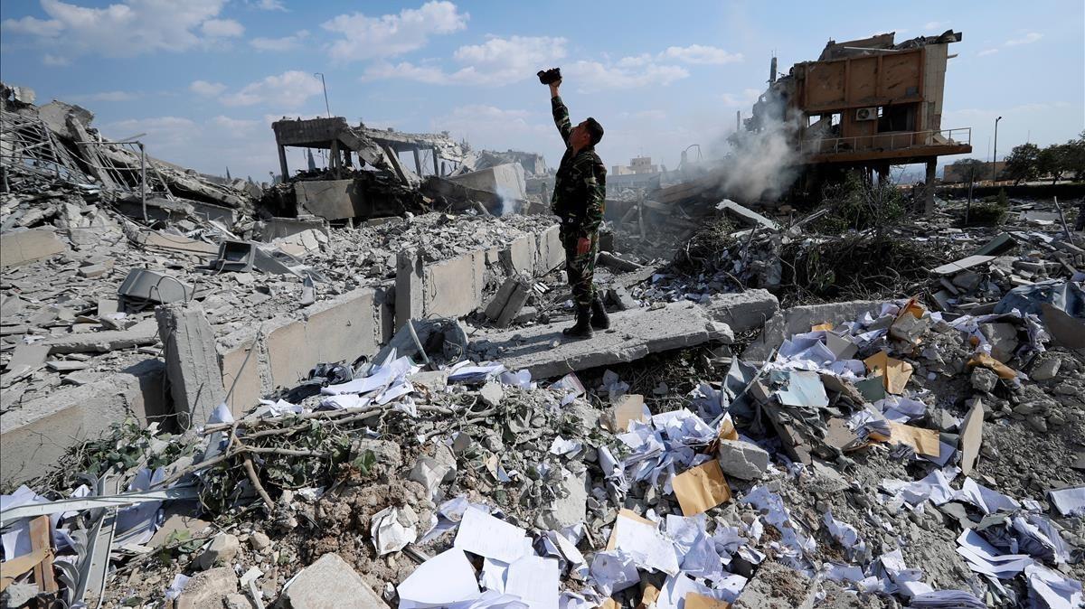 Un soldado sirio filma los escombros tras un ataquede las fuerzas estadounidenses, francesas y británicas el 14 de abril del 2018 para castigar al presidente Bashar el Asad por el uso de armas químicas contra civiles.