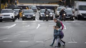 Un padre agarra a sus hijos para cruzar la calle de Aragó, probablemente, la más peligrosa de Barcelona