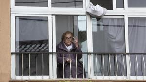Otilia Augusta saluda con el signo de victoria desde su domicilio en el barrio de Singuerlín en Santa Coloma de Gramenet.