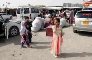 Tres menores afganos esperan en un puesto fronterizo pasar junto a su familia a la vecina Pakistán.