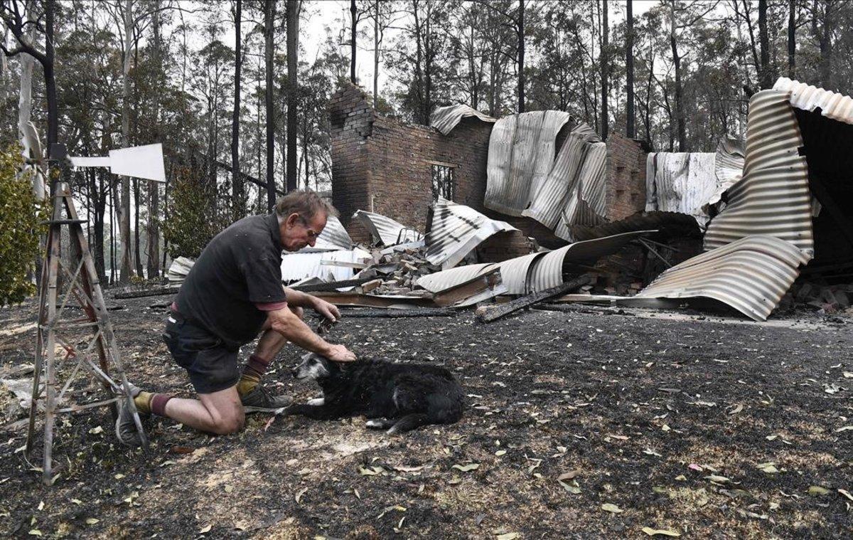 Un hombre, acompañado de su perro, retorna a su casa destruida por el fuego en Nana Glen, a 600 kilómetros de Sídney.