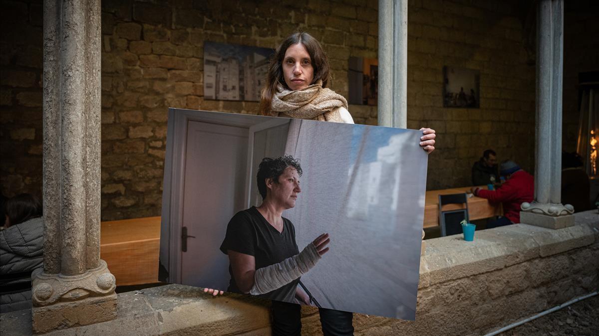 Maria Contreras Coll, en el claustro de Santa Anna con una de las imágenes de su exposición sobre la ayuda que ofrece la parroquia a los afectados por el covid-19..