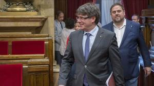 El presidente de la Generalitat, Carles Puigdemont, y el vicepresidente del Govern, Oriol Junqueras, en el hemiciclo del Parlament.