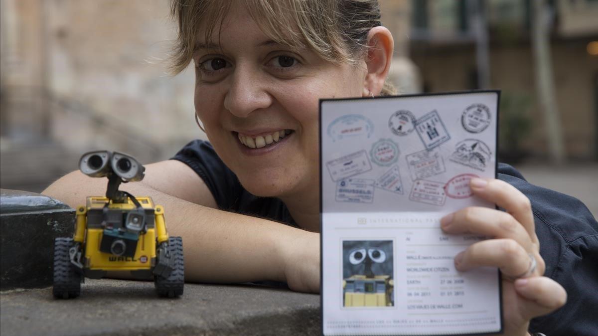 Júlia Vázquezenseña el pasaporte de su Wall-E viajero. A su derecha, el muñeco trotamundos con cámaraal cuello.