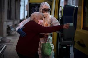Trabajadores sanitarios trasladana ancianos.