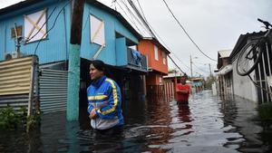 Dos personas caminan por una calle inundada en Juana Matos (Puerto Rico), el 21 de septiembre.