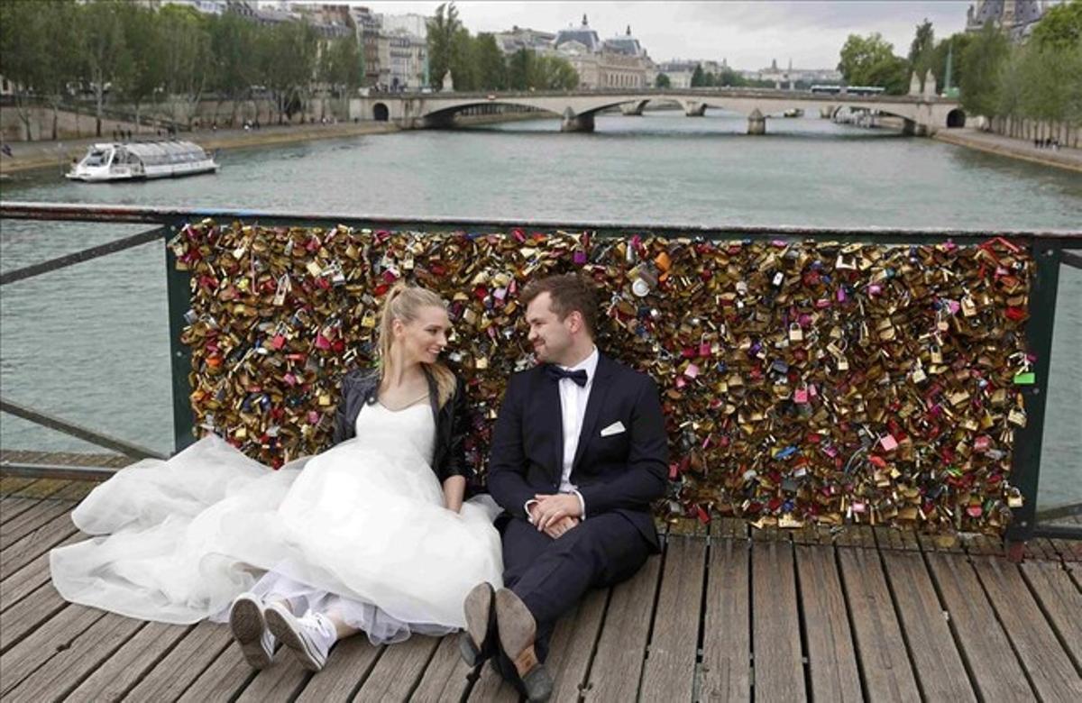 Una pareja de recién casados sentados frente a una de las barandillas repletas de candados del puente de las Artes, en París, el domingo 31 de mayo. Las autoridades han empezado a retirar los candados el 1 de junio.