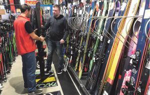 Un especialista de la tienda L'Iglú de Barcelona recomienda unos esquís a un cliente.
