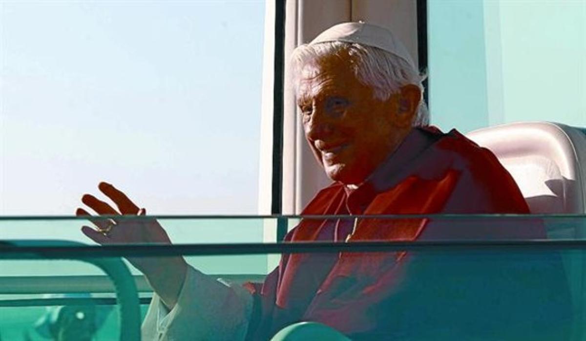 Benedicto XVI saluda desde el 'papamóvil', ayer al llegar a Cuatro Vientos, antes de la misa.