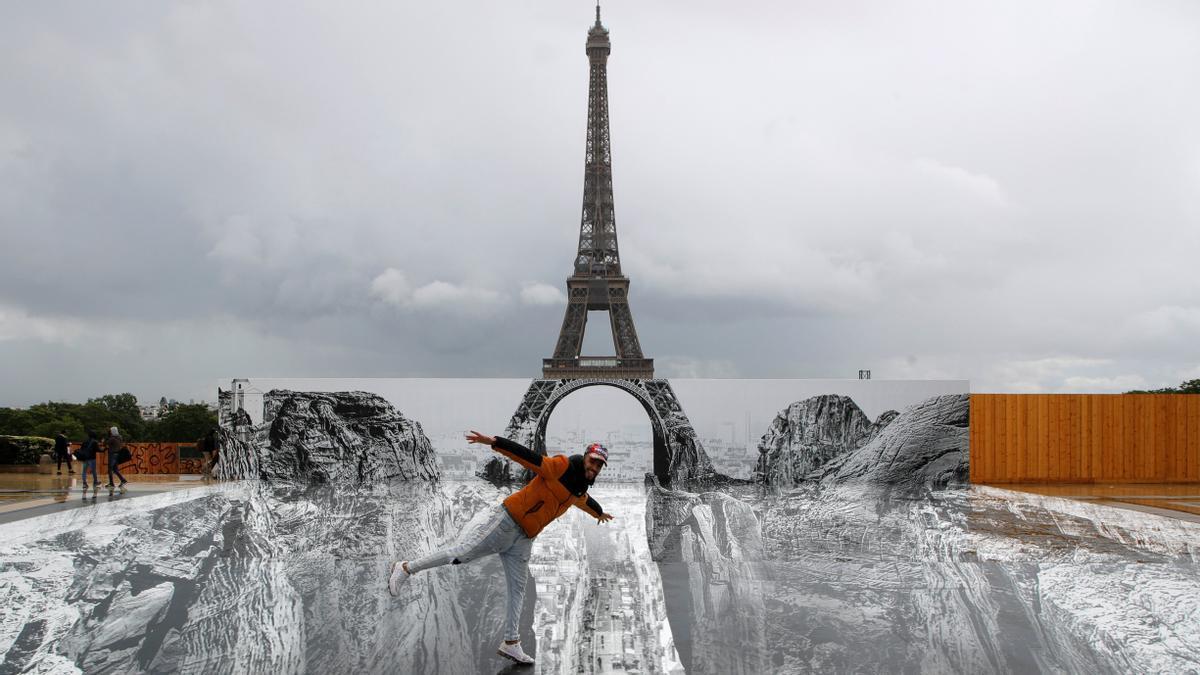 Un hombre posa en una instalación artística gigante colocada ante la torre Eiffel.