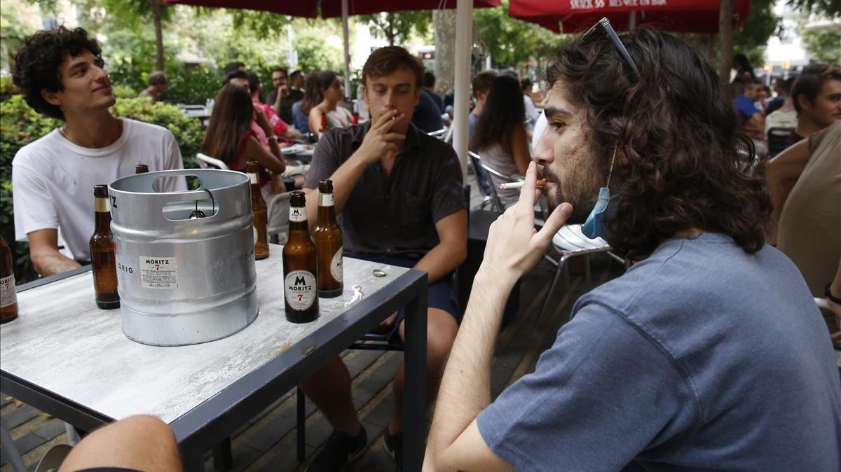 Jóvenes fumando en la terraza de un bar, en el paseo de Sant Joan, Barcelona.