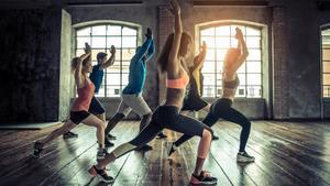 Gente practicando deporte en un gimnasio.