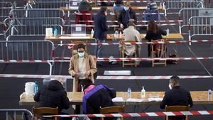 Varias personas votan en el colegio electoral del polideportivo municipal de Palau en Girona, a primera hora de este domingo.